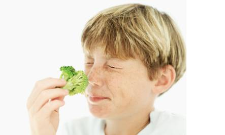 boy smelling broccoli