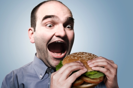 guy eating bi hamburger with bun