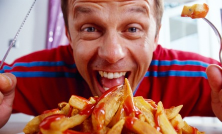 man digs into a plate of the most fattening foods, french fried potatoes