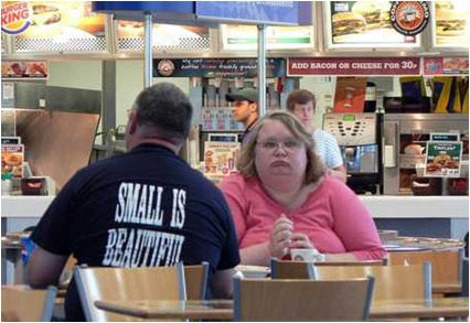 couple sits in a fast food restaurant with many fattening foods as options