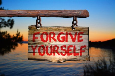 Forgive yourself sign on old wood with a blurred sunset sky and sea on background