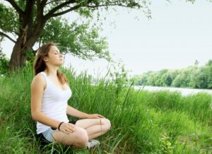 young woman sits in meditation under a tree focusing on her breath